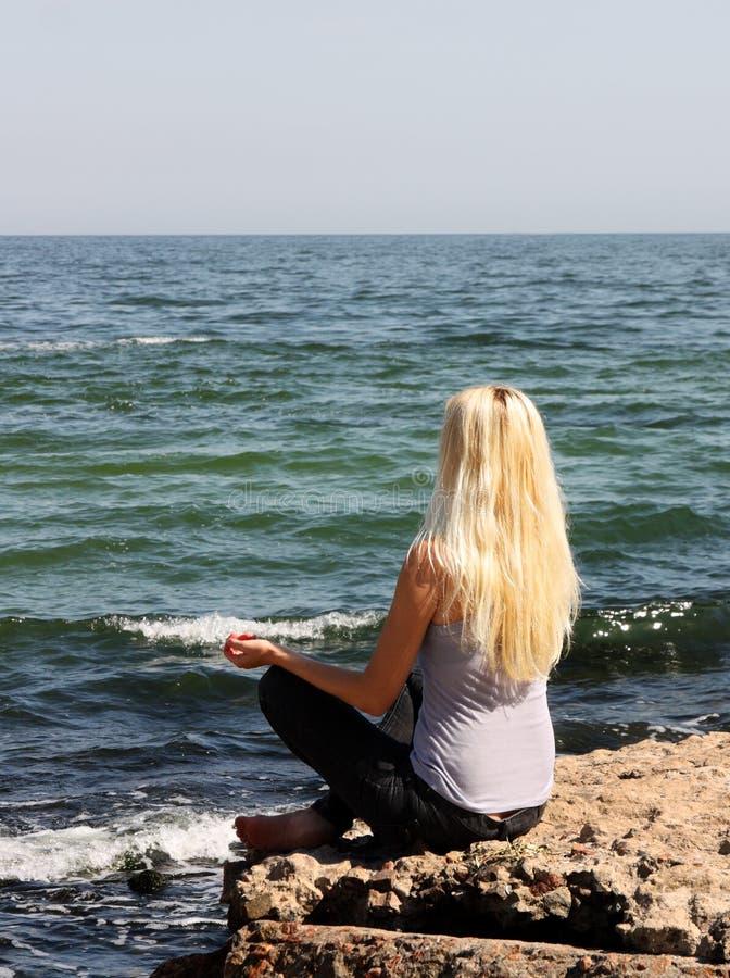 Meditazione vicino al mare fotografia stock