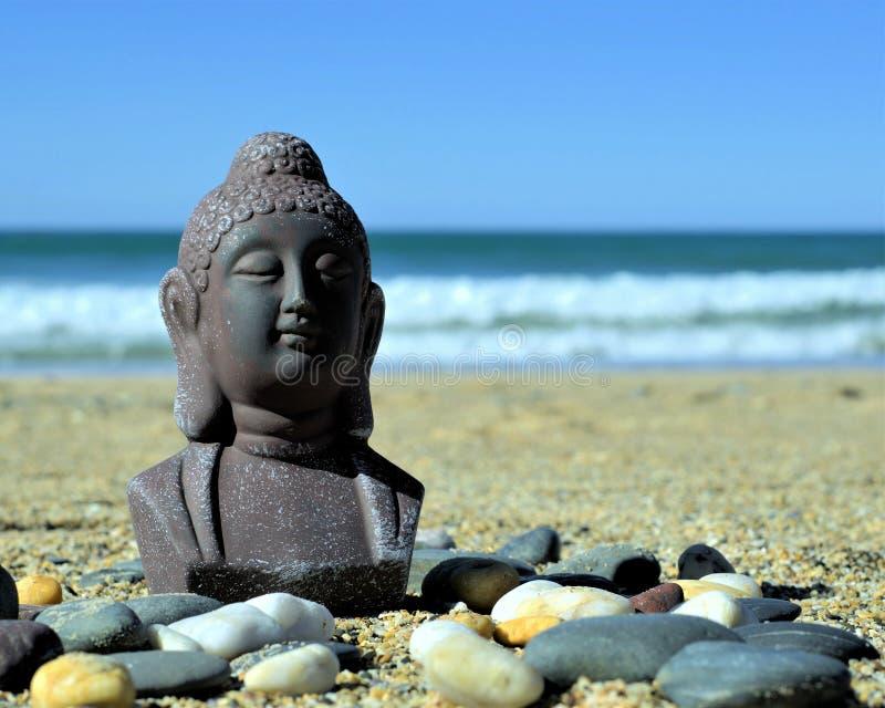 Meditera Buddhastatyn på sand royaltyfria foton