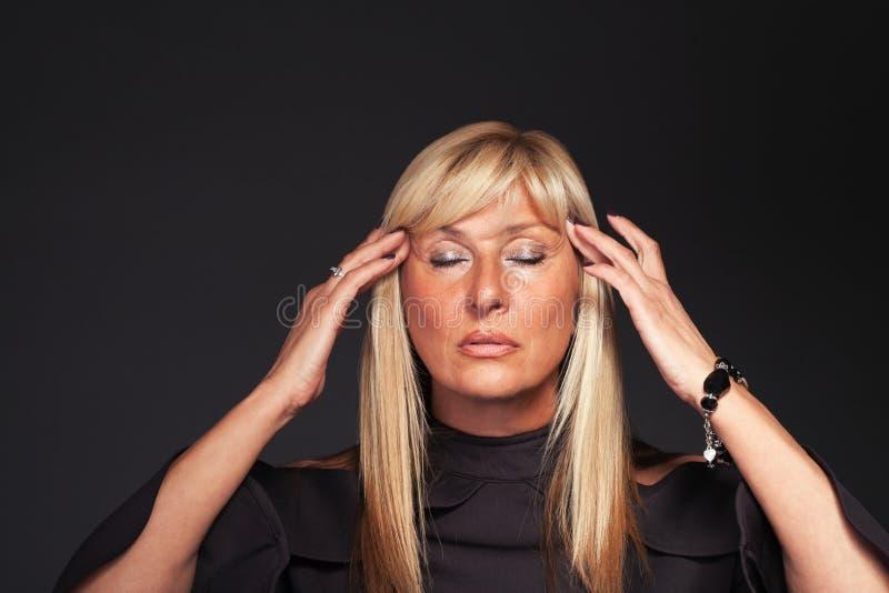 Meditera den åldriga kvinnaståenden för blond mitt arkivfoton