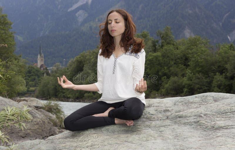 Meditera den unga kvinnan utomhus i natur royaltyfri bild