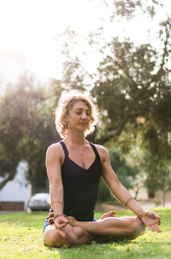 Meditera för kvinna och praktiserande yoga, Padmasana Meditation på Sunny Autumn Day At Park utomhus- genomkörare royaltyfri fotografi