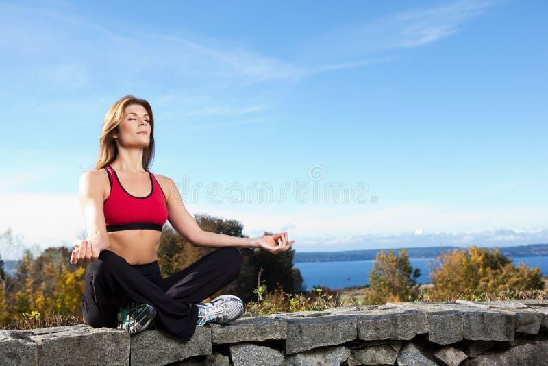 meditera kvinnayoga royaltyfria bilder