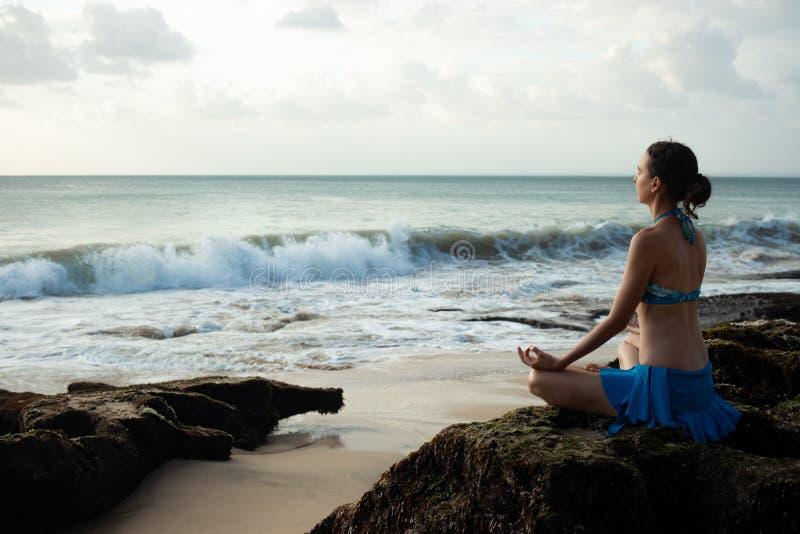 Meditera praktiserande yoga för ung kvinna och pranayama med den gyan mudraen på stranden, Bali royaltyfri bild