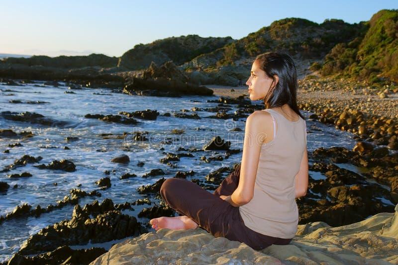 Het mediteren van gekleurd meisje op overzeese kust stock afbeelding