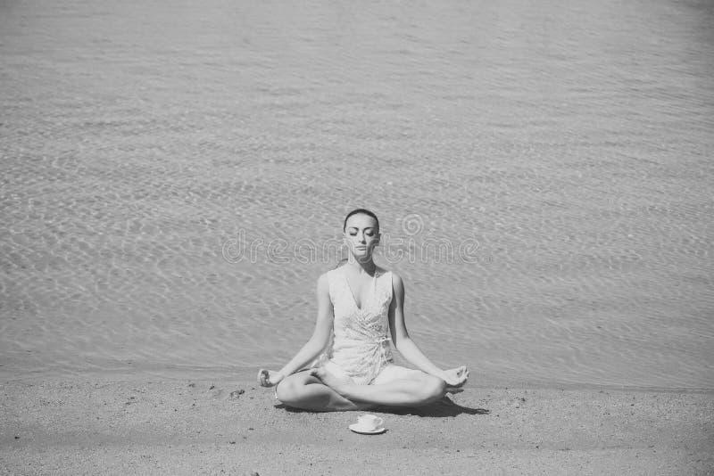 Mediterende vrouw vrouw het mediteren in yoga stelt met koffiekop bij water stock afbeelding