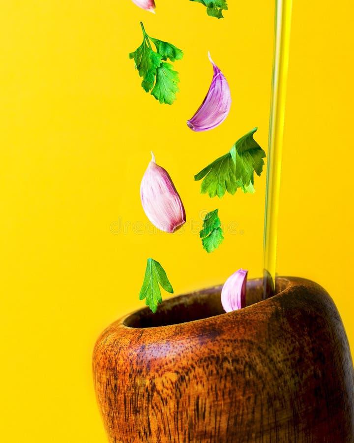 Mediterraan dieetconcept Knoflook, peterselie en olie die in een houten mortier vallen stock foto