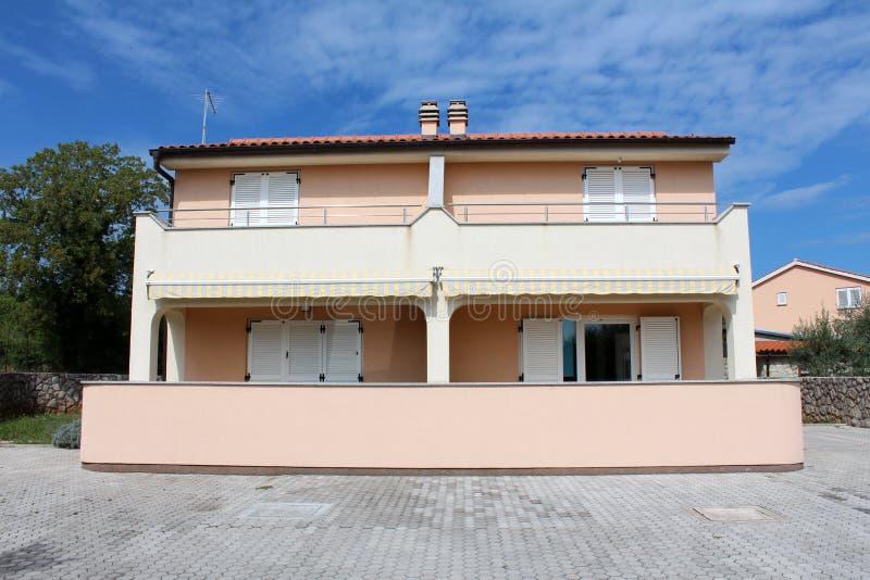 Mediterrane die villa met vier flats en grote voordiebalcones wordt verdeeld met steentegels worden omringd en bomen met binnen h stock foto's