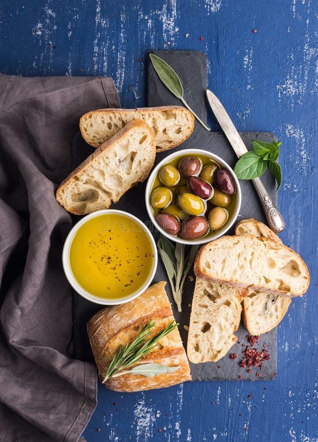 Mediterrane geplaatste snacks Olijven, olie, kruiden en gesneden ciabattabrood op de zwarte raad van de leisteen over geschilderd stock foto
