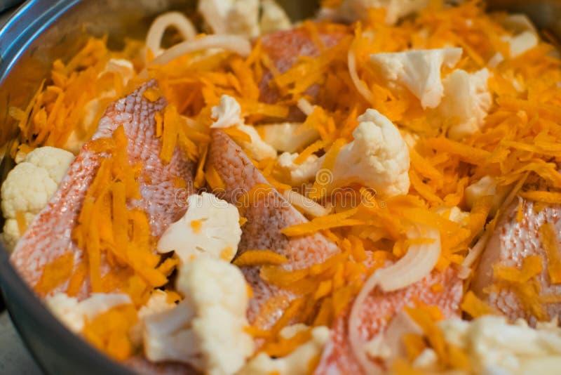 Mediterrane overzeese baarzen met bloemkool en wortelen in een pan Het koken procédé stock afbeelding