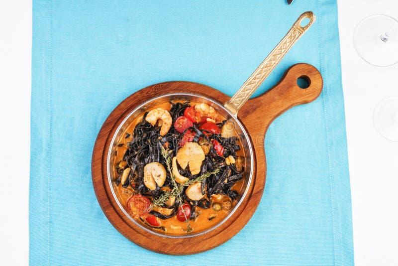Mediterrane schwarze Pasta mit Garnelen, Tomaten, Knödel, Rosmarin und Pilzen lizenzfreie stockfotografie