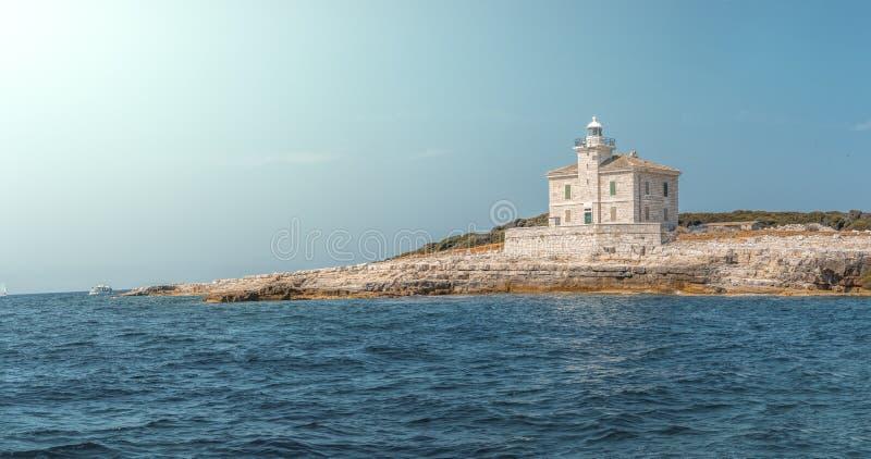 Mediterrane Vuurtoren op de kustlijn stock fotografie
