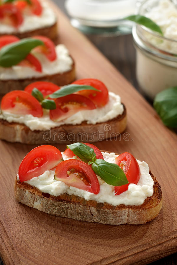 Mediterranean appetizer bruschetta with cheese, tomato and basil on cutting board. Italian snack with ciabatta, feta, vegetable and herb stock image