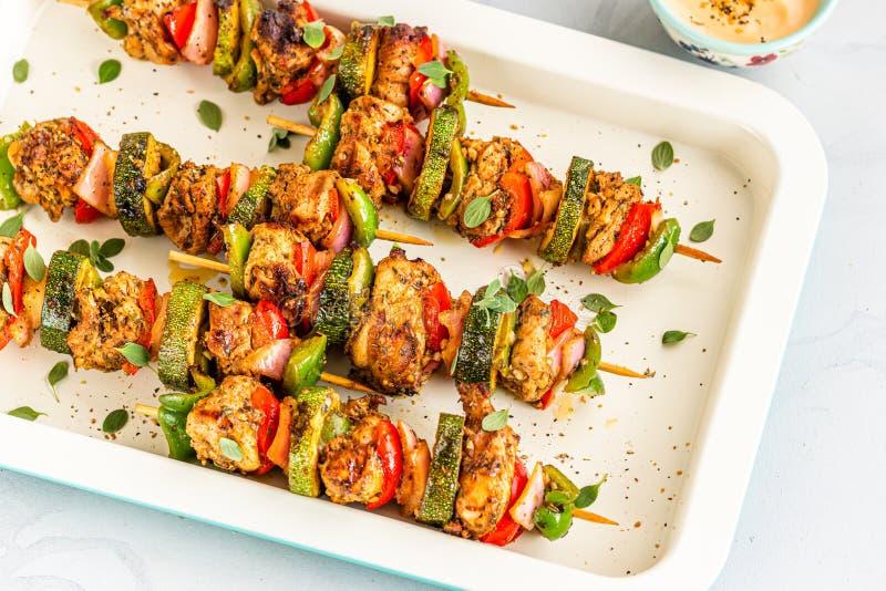 Skewered on Wooden Sticks Greek / Mediterranean Chicken Kebabs Grilled Meat on White Baking Sheet with Sauce. stock photo