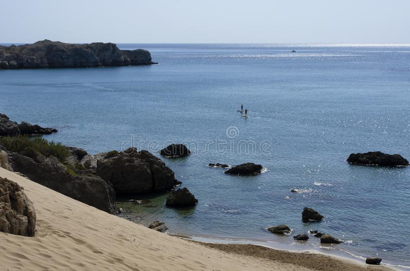 Mediterranean coast with unidentified tourists engaged standup paddleboarding stock image