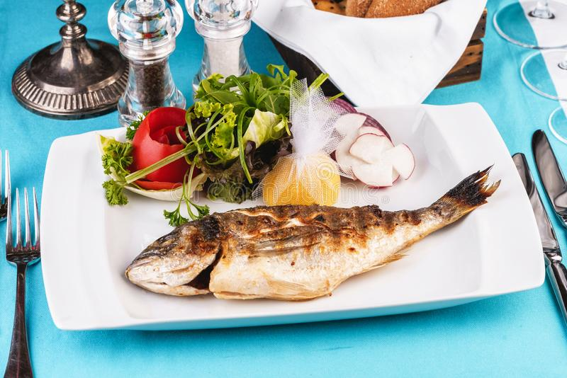 Rainbow trout, grilled, served with vegetables royalty free stock photo
