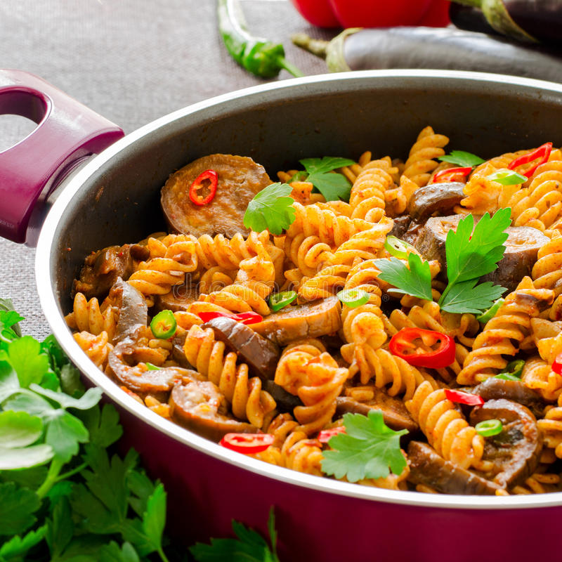 Download Mediterranean Eggplant Pasta In Pot With Tomatoes, Red Pepper And  Parsley On Grey Background