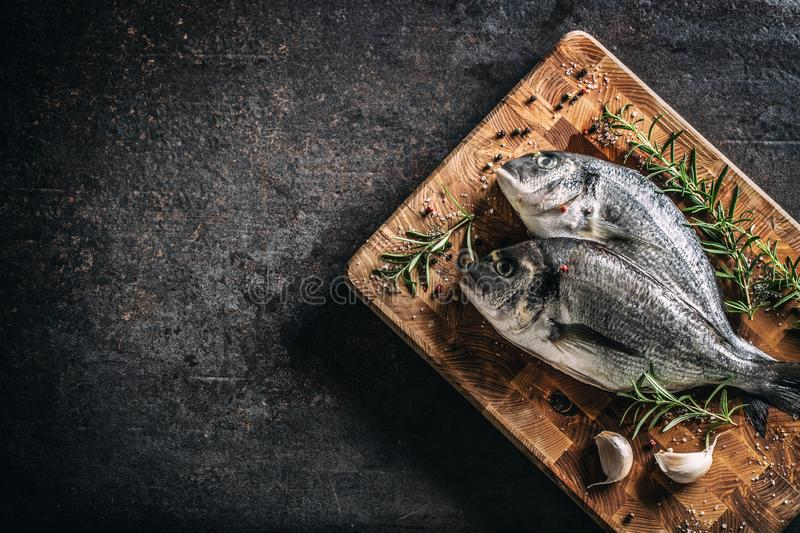 Mediterranean fish bream with spices salt herbs garlic and lemon. Healthy seafood. Concept of healthy sea food.  royalty free stock images