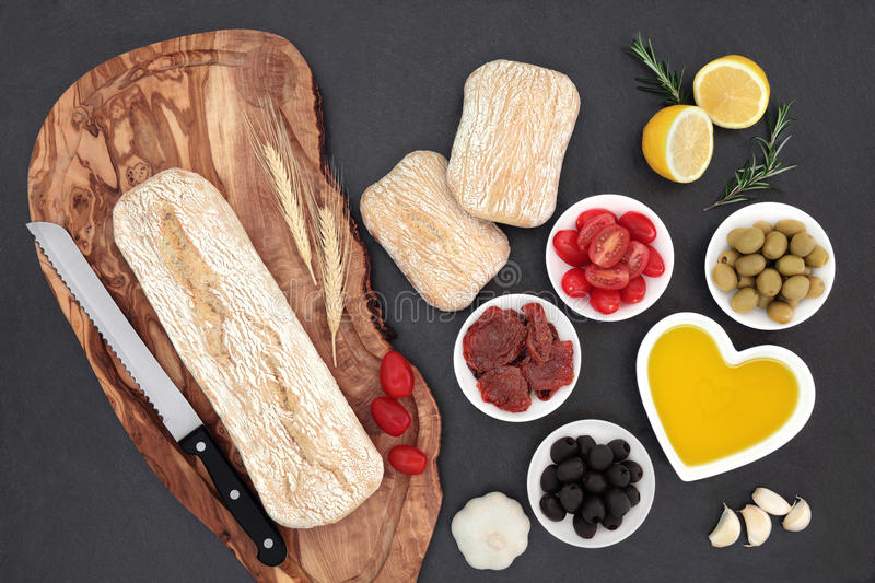Mediterranean Food. With olives, fresh and sundried tomatoes, garlic, lemon, oil and ciabatta bread on olive wood board with wheat sheaths and rolls stock photo