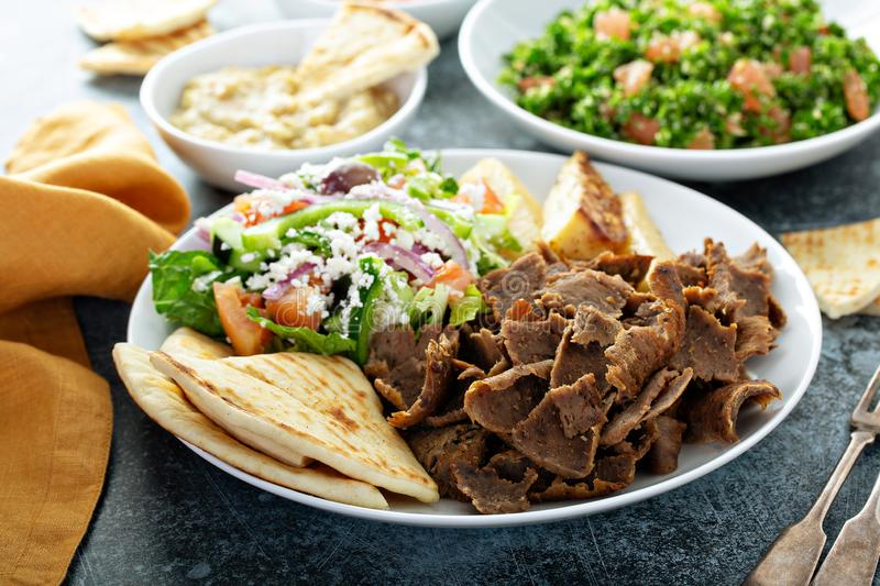 Mediterranean food on the table. Gyro platter, pita and dips and tabbouleh royalty free stock photography