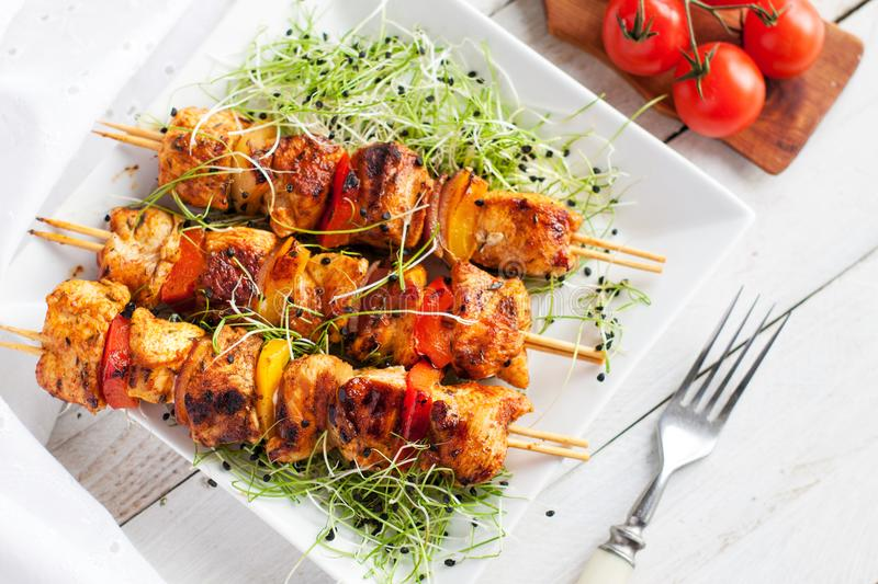 Mediterranean grilled chicken skewers. Served with microgreen and cherry tomatoes stock photo