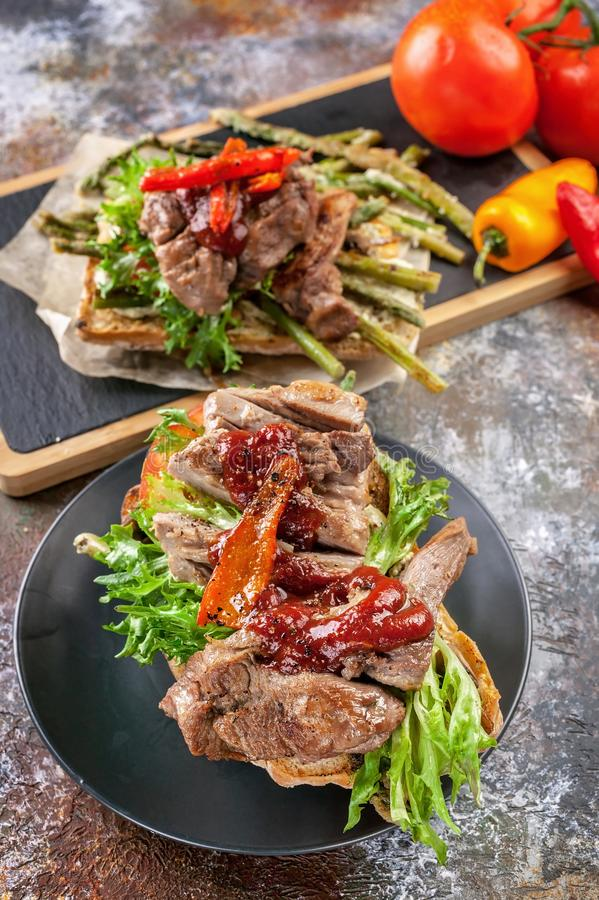 Mediterranean Kitchen. Vertical shot. Grilled turkey meat on a traditional chabbata with sweet peppers, tomatoes and herbs on a. Cutting board stock photo