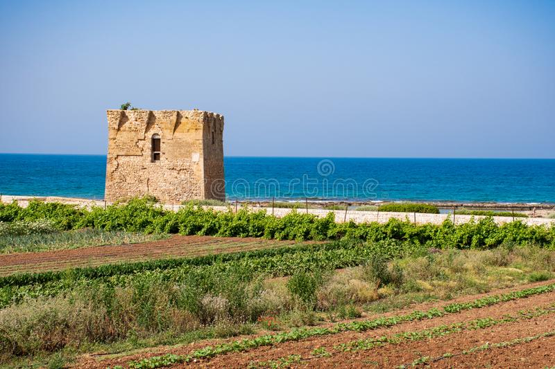 Mediterranean landscape, Puglia. Baroque watchtower, beautiful old tower in San Vito, Polignano a Mare, Bari, Puglia, Italy with with blue sea, beach and royalty free stock image