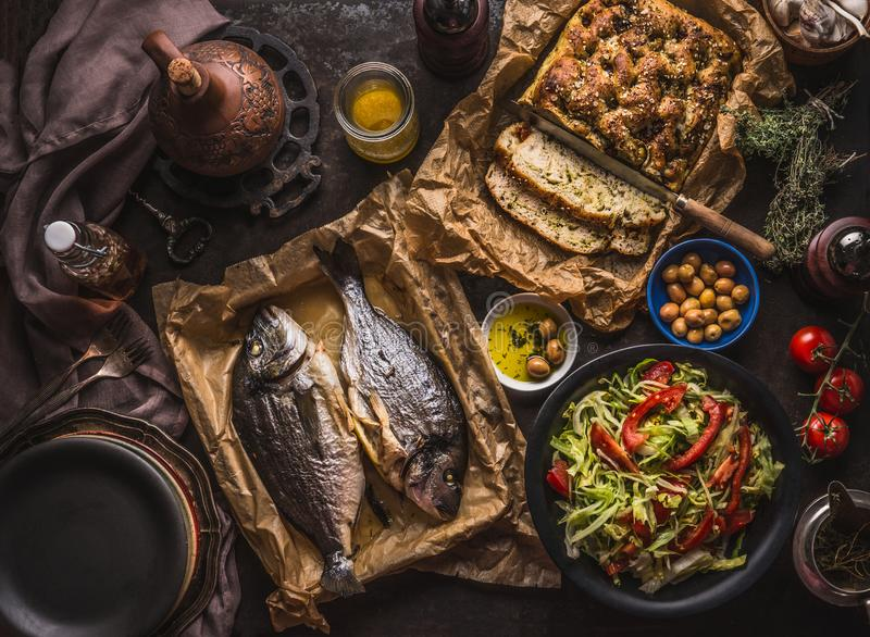 Mediterranean lunch or dinner with roasted dorado fishes, homemade focaccia bread , olive oil and olives served on rustic table royalty free stock photography