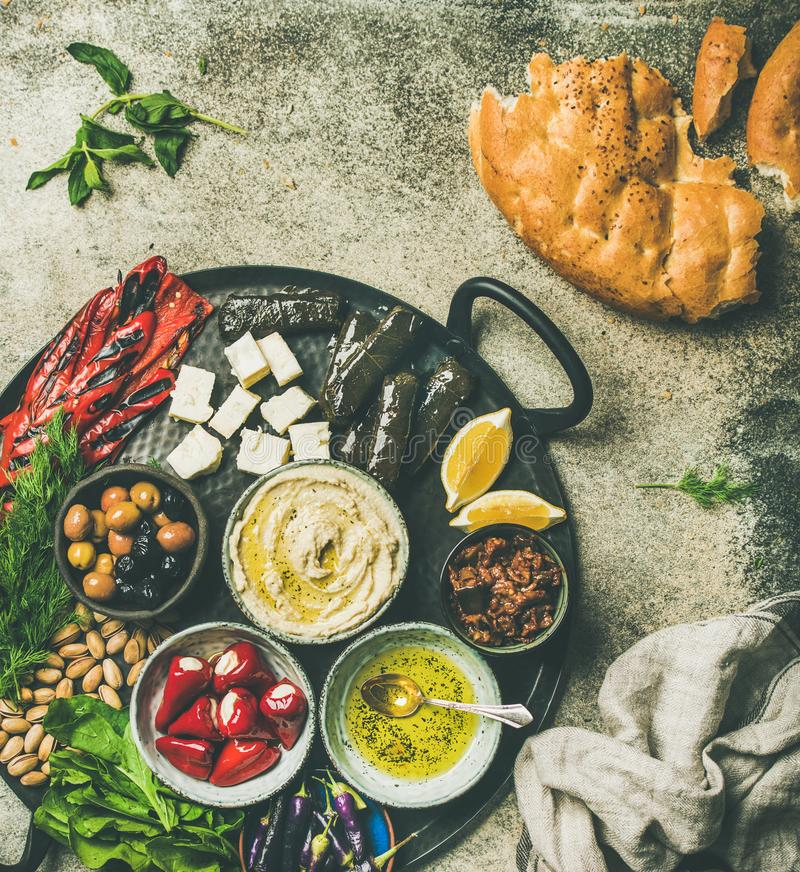 Mediterranean meze starter fingerfood platter in tray. Mediterranean, Middle Eastern meze starters platter. Flat-lay of stuffed pickled paprikas, dolma, hummus royalty free stock photo