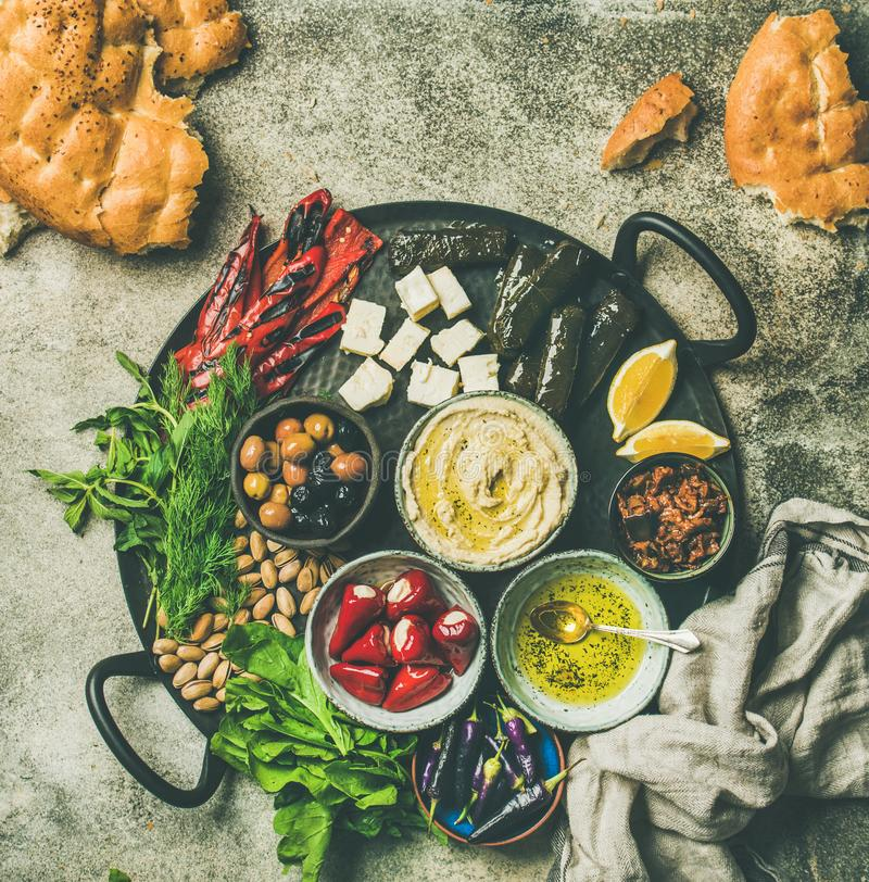 Mediterranean meze starter fingerfood platter, copy space. Mediterranean, Middle Eastern meze starters platter. Flat-lay of stuffed pickled paprikas, cheese royalty free stock image