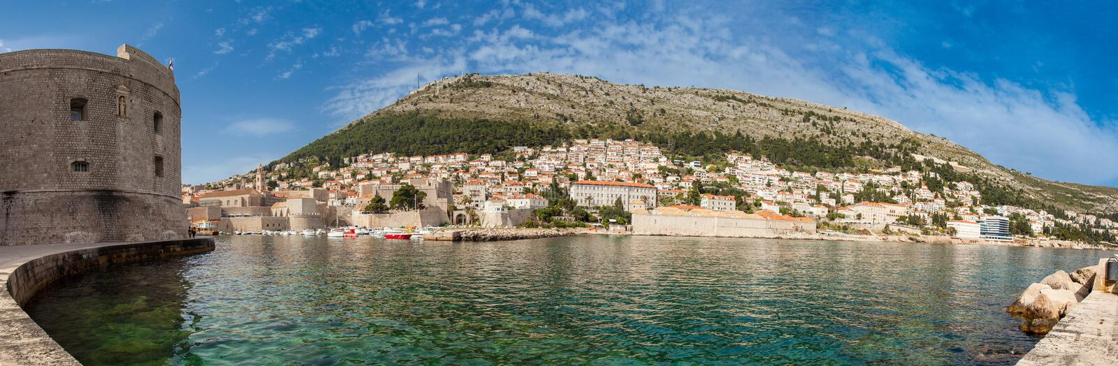 Mediterranean panorama of Dubrovnik old city including the old port, city walls and fortifications. Mediterranean panorama of the beautiful Dubrovnik old city stock photos