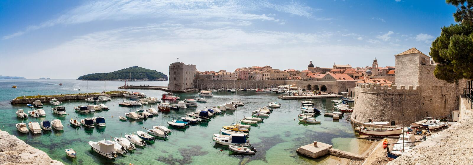 Mediterranean panorama of Dubrovnik old city including the old port, city walls and fortifications. Mediterranean panorama of the beautiful Dubrovnik old city stock image