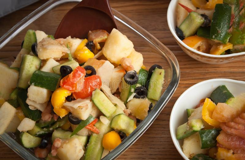 Mediterranean potatoes with olives and a variety of fresh vegetables, served with some fresh salads stock photo