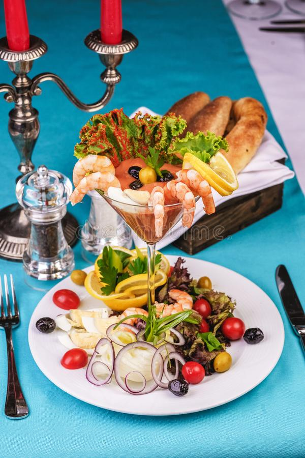 Mediterranean prawn appetizer with greens, lemons served with tomatoes, onions, olives, quail eggs and vegetables royalty free stock photos