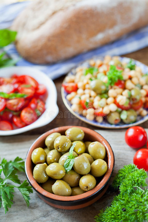 Mediterranean salad board - cherry tomatoes, green olives, chick. Green olives with olive oil and basil in brown dish on wooden background. Cherry tomatoes and stock photos