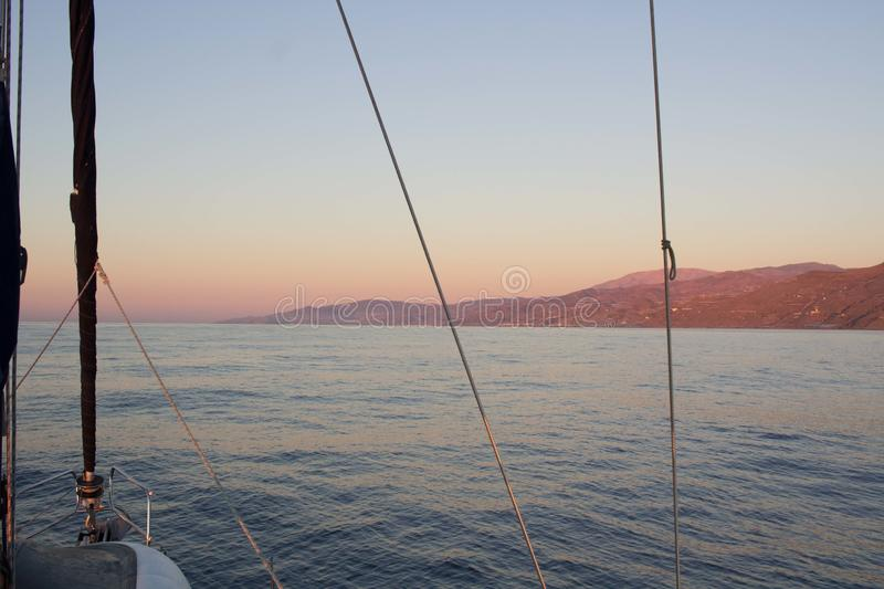 Mediterranean sea sunset view to coast from sailing yacht royalty free stock photography