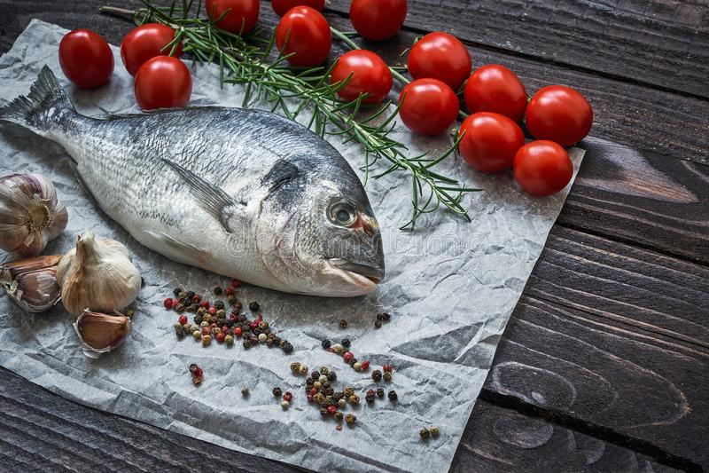 Raw dorado fish with garlic and tomatoes on rustic background. Sea bream or dorada fish. Top view, copy space. Mediterranean seafood concept. Raw dorado fish royalty free stock photos