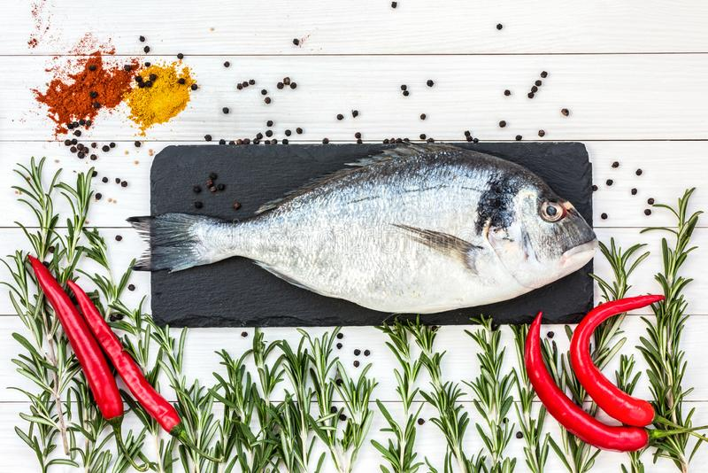 Mediterranean seafood concept. Raw dorado fish with peper and rosemary on white wooden table. Copy space, view from above. Mediterranean seafood concept. Raw royalty free stock images