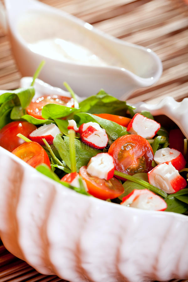 Mediterranean seafood salad. With spinach leaves, cherry tomatos and surimi and mayonnaise sauce royalty free stock photography