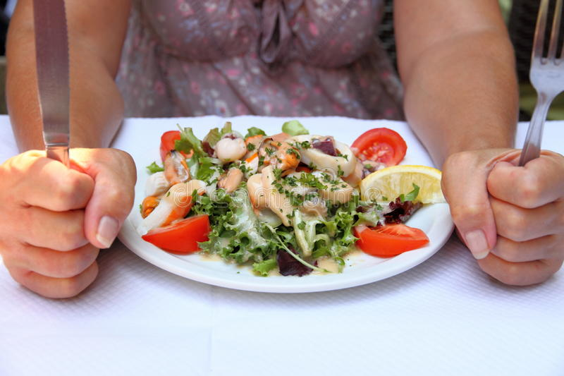 Mediterranean seafood salad and woman with knife and fork. Concept of health stock image