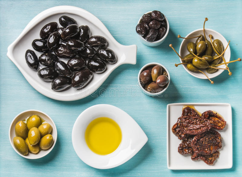 Mediterranean snack assortment. Black and green Greek olives, capers, olive oil, sun-dried tomatoes over turquoise blue. Mediterranean snack assortment. Black stock images
