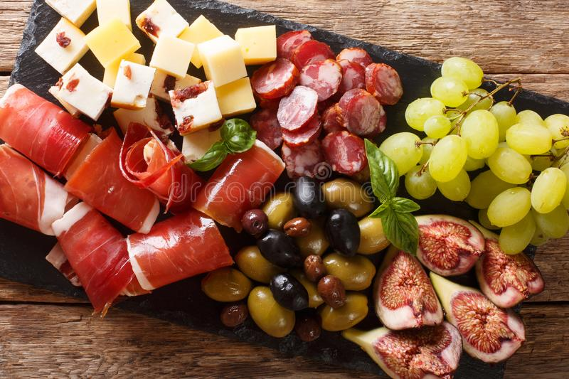 Mediterranean snack of cheese platter, prosciutto ham, grapes, figs, sausages and olives. horizontal top view stock photo