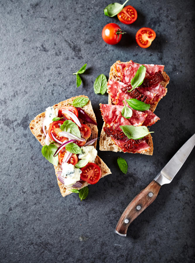 Mediterranean-style ciabatta sandwiches with salami, dried tomatoes, gorgonzola and cherry tomatoes stock images