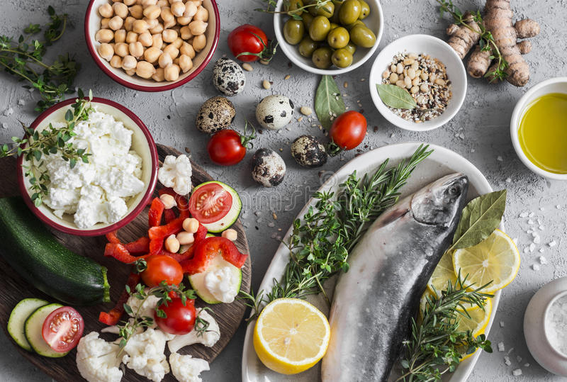 Mediterranean style food background. Fish, vegetables, herbs, chickpeas, olives, cheese on grey background, top view. Healthy food royalty free stock image