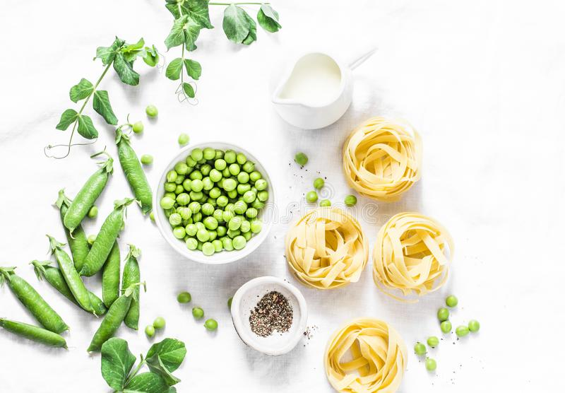 Mediterranean style healthy food ingredients for cooking lunch - fettuccine pasta, fresh green peas, cream, spices on a light back royalty free stock image