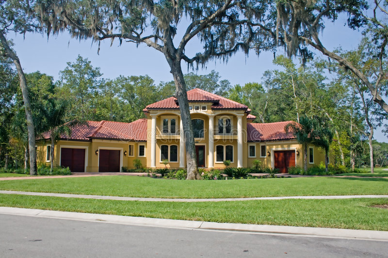 Mediterranean style home. Tile roofed luxury estate style home under shady oak trees stock photo