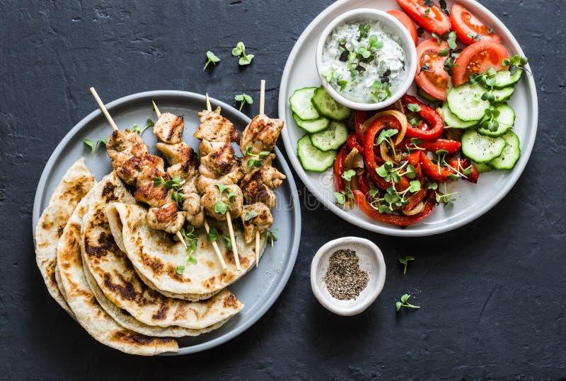 Mediterranean style lunch table - turkey skewers, flatbread, tomatoes, cucumber salad, baked sweet pepper, yogurt herb sauce  on a. Dark background, top royalty free stock images