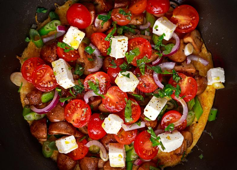 Mediterranean style omelet in frying pan with feta cheese, cherry tomatoes, red onions, mushrooms, spring onions and parsley. stock photography