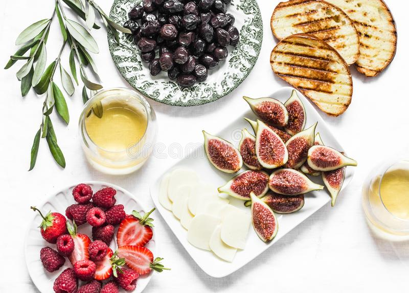 Mediterranean style snack appetizers - dried olives, figs, cheese, grilled bread, strawberries, raspberries and white wine on a royalty free stock photo