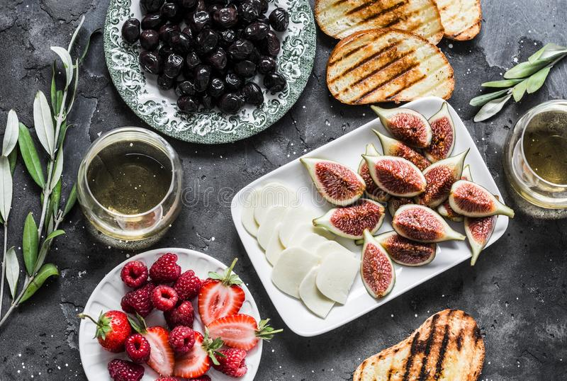 Mediterranean style snack appetizers - dried olives, figs, cheese, grilled bread, strawberries, raspberries and white wine on a. Dark background, top view stock photography