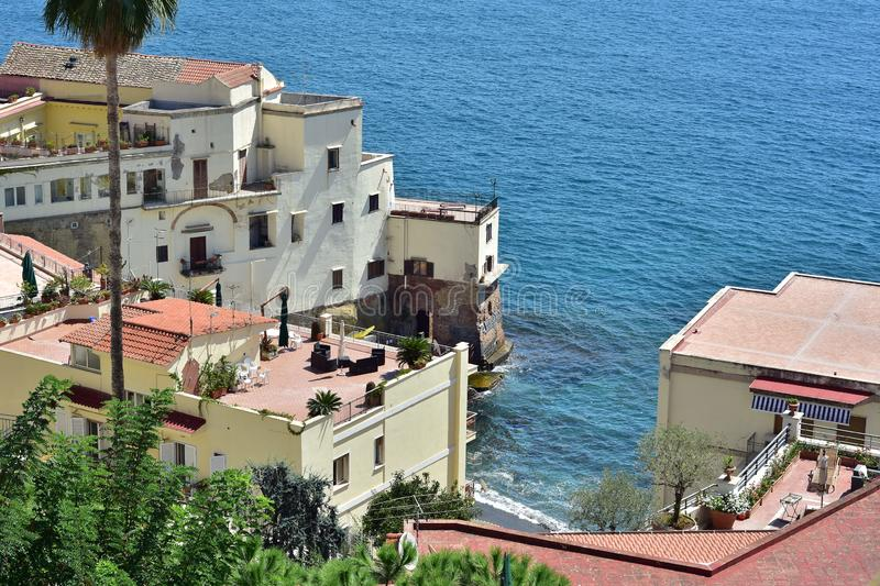 Terrace houses on rocky coast. Mediterranean terrace houses build on steep rocky cliffs along rugged coast with beautiful views of blue sea royalty free stock image